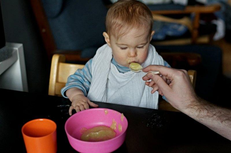 Baby beim essen mit Kindergeschirr
