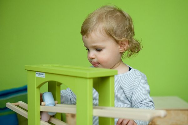 Ein Kind lässt Holzfiguren auf der Murmelbahn rollen