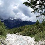 Flusslauf vor wolkenverhangenen Alpen
