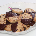 Runde Cranberry-Zitronen-Taler, halb in Schokolade getaucht liegen in einer weißen ovalen Porzellanschale