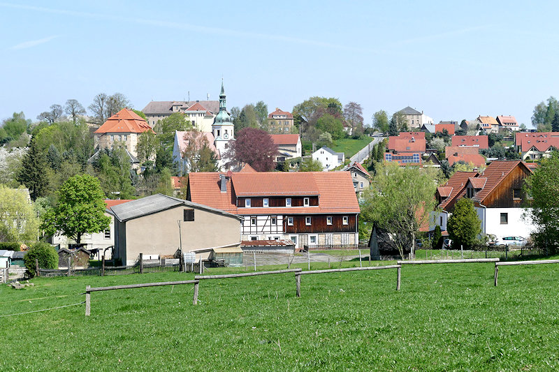 Struppen, grüne Weidefläche, anschließend ein Wirtschaftsgebäude dahinter ein Fachwerkhaus, im Hintergrund Kirche und Wohnhäuser