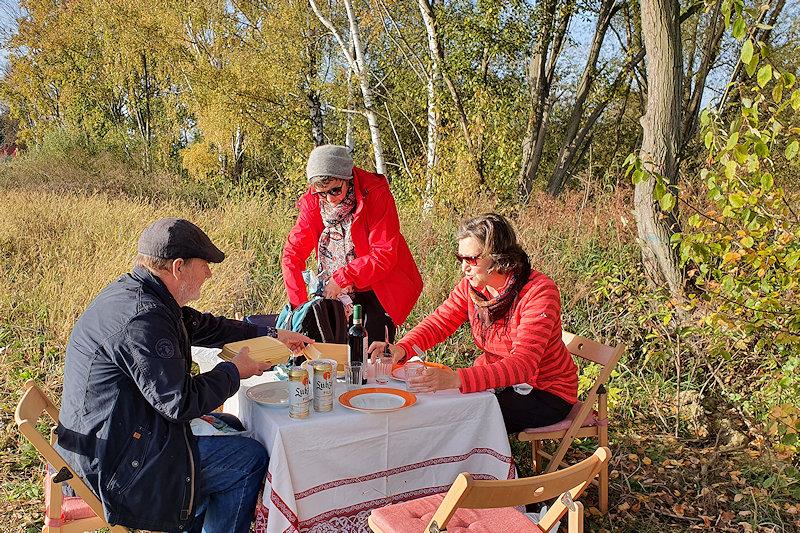 Auf einer Herbstwiese wird ein Campingtisch mit Tellern, Gläser und einer Flasche Rotwein gedeckt. In der beigen Assiette ist der Gänsebraten.