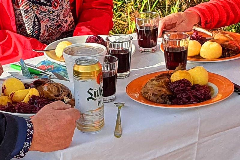 Ein Tisch mit vier Tellern auf denen ein Gänsekeule zwei Klöße und Rotkraut liegen. Außerdem vier Gläser mit Rotwein.