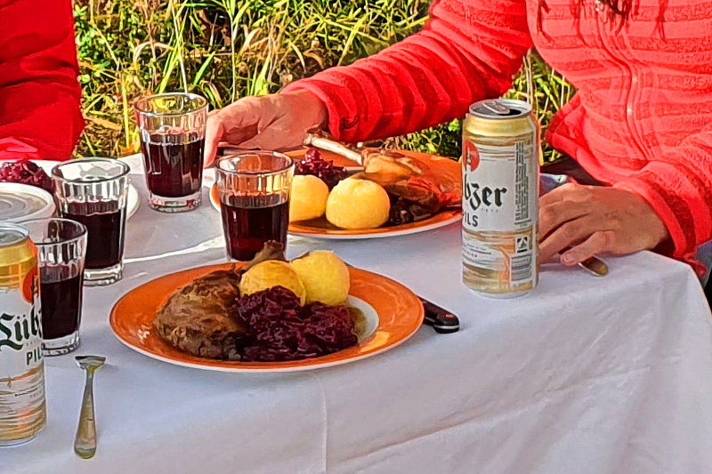 Üppig gedeckter Tisch im Freien mit Gänsebratentellern, Rotweingläsern und Bierdose.