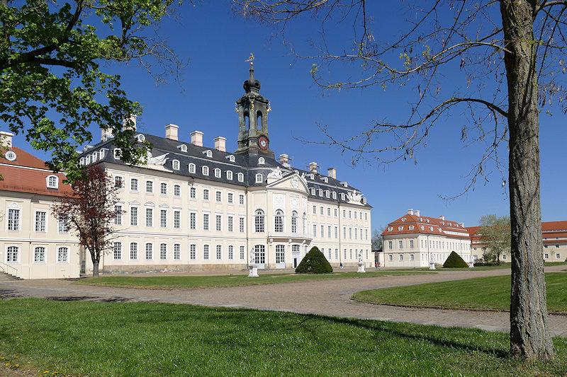 Schloss Hubertusburg bei blauem Himmel, im Vordergrund Wiese und zwei Bäume.