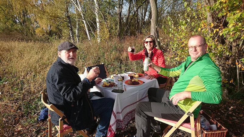 Meine Cousine und unsere Männer prosten mit Rotwein bzw. Bier in die Kamera. Sie sitzen um unseren gedeckten Gänsebraten-Tisch.